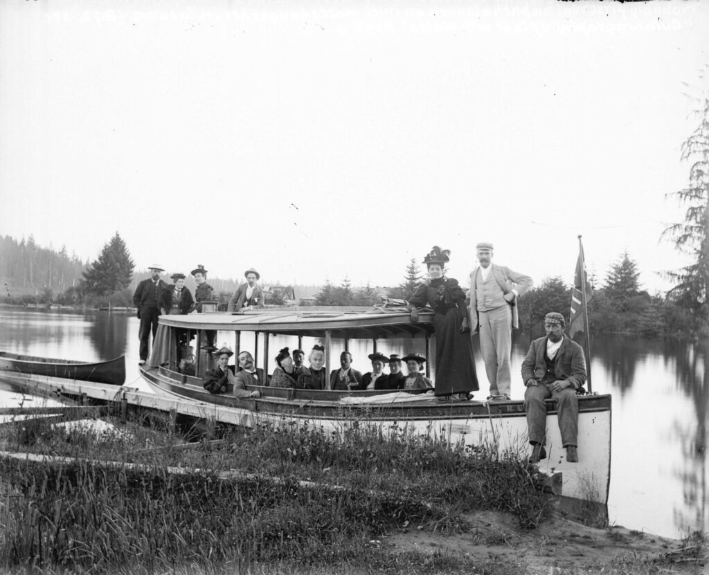 """Men and women on Captain William Watts' gasoline launch """"Ruth"""" at bank of Lynn Creek, ca. 1896"""