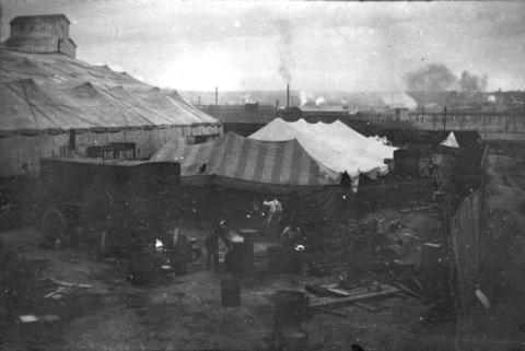 men cooking around circus tent